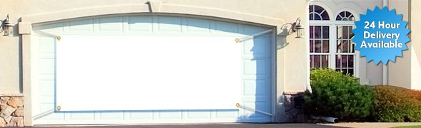 A double garage door with a 10 foot personalised banner hung across it.
